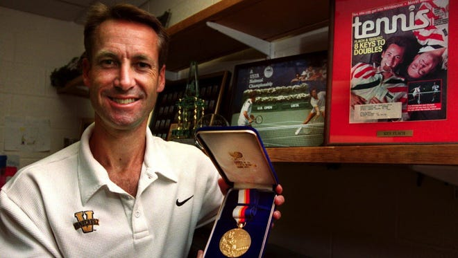 This file photo from 2002 shows Ken Flach displaying his 1988 Olympic gold medal along with other memorabilia in his office.