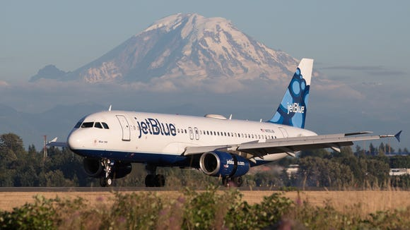 A jetBlue Airbus A320 lands in view of Mount Rainier