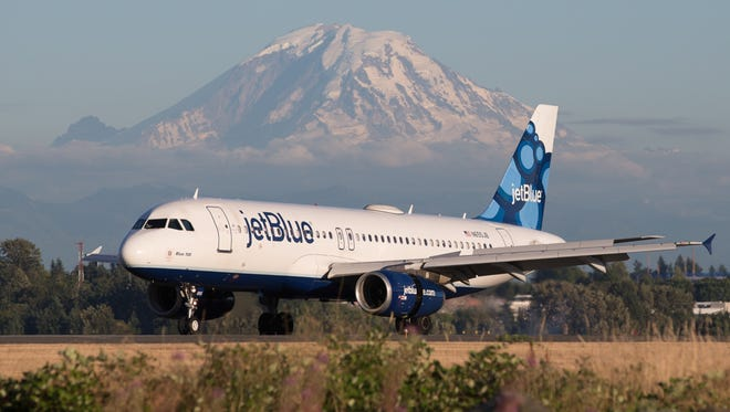 A jetBlue Airbus A320 lands in view of Mount Rainier at Seattle-Tacoma International Airport in July 2017.