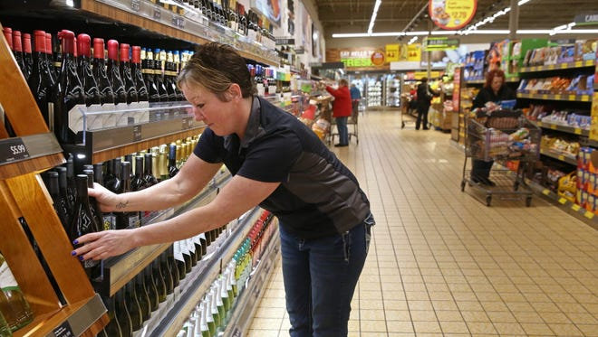Sandy Rosploch, shift manager, arranges a wine display at the Aldi store at 6925 Durand Ave. in Racine.