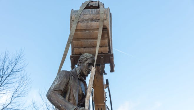 The mouth of a backhoe positioned over the statue. RENEE ROSENSTEEL / FOR THE INCLINE