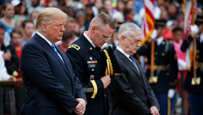 President Trump, left, Maj. Gen. Michael L. Howard, commanding general of Joint Force Headquarters-Nationa­l Capital Region and the Military District of Washington, center, and Secretary of Defense Jim Mattis pray during a Memorial Day wreath laying ceremony at Arlington National Cemetery on May 28, 2018, in Arlington, Va.