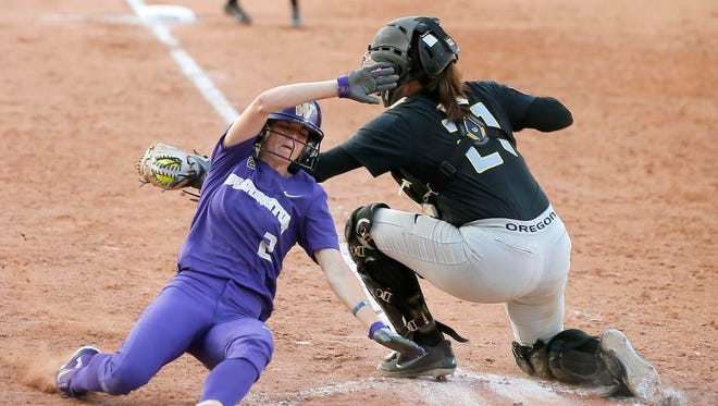 Washington's Trysten Melhart (2) slides home past Oregon's Gwen Svekis (21) during an NCAA softball Women's College World Series game in Oklahoma City, Friday, June 1, 2018. Melhart scored on the play after Oregon was called for obstruction. (Bryan Terry/The Oklahoman via AP)