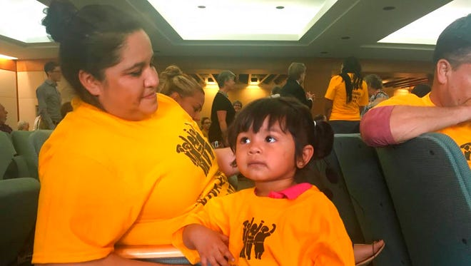 Two-year-old Amanda Ordonez, center, and her baby sitter, Veronica Velazquez await the start of a hearing in Santa Fe, N.M., where lawmakers heard testimony about conditions inside federal detention facilities in the state, Monday, July 16, 2018. Lawmakers held a hearing to take testimony about conditions inside the facilities and to weigh how they might exert more oversight at the state level over privately operated detention centers for migrants in New Mexico, where U.S. Immigration and Customs Enforcement has agreements with private companies and counties to operate the facilities.