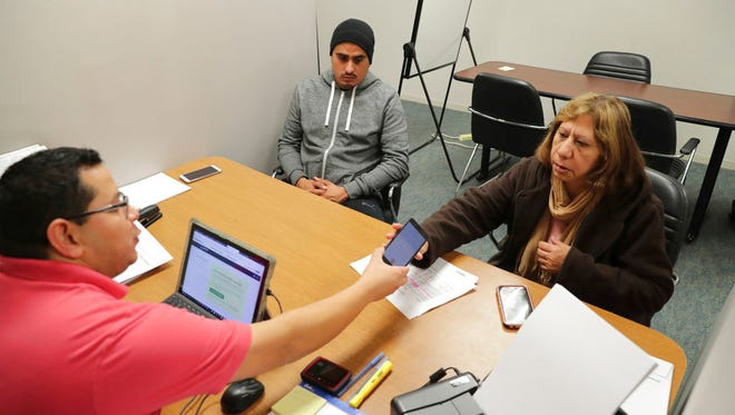 In this Dec. 27, 2017, file photo, Community Council health care navigator Fidel Castro Hernandez, left, hands a Spanish help line phone to legal U.S. resident Maria Ana Pina, right, as she signs up for the Affordable Care Act with her son Roberto Pina at the Community Council offices in Dallas. A new poll finds that more than half of Hispanic adults have encountered a communication barrier in the health care system.