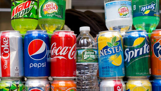 Cans of soda and bottled water are displayed on a food cart, Monday, May 7, 2018 in New York. (AP Photo/Mark Lennihan)