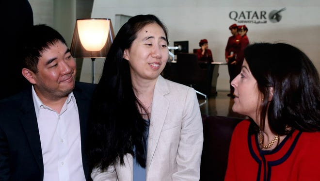 American couple Grace, center, and Matthew Huang speak with U.S. Ambassador to Qatar, Dana Shell Smith,  at the Hamad International Airport in Doha, Qatar, before their departure for Los Angeles, on Wednesday, Dec. 3, 2014.