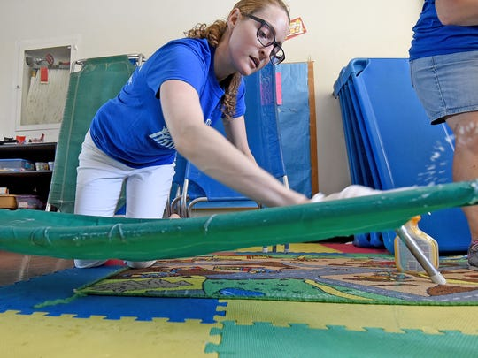 Brandel Boyd from North Central State College wipes down children's cots Friday morning at the Friendly House as part of the United Way Day of Service.