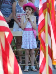 This young girl watches as a wreath is placed at the entrance to the Marion County World War II Veterans Memorial on Monday in Marion Cemetery.
