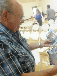 Bill Kennedy looks through pictures of the flooding