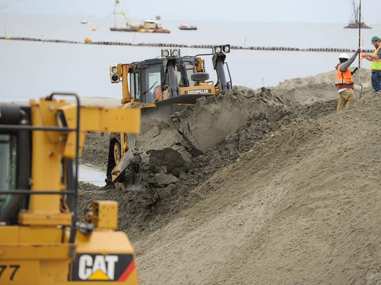 A bulldozer pushes sand onto Broadkill Beach that was dredged from the Delaware Bay shipping channel.