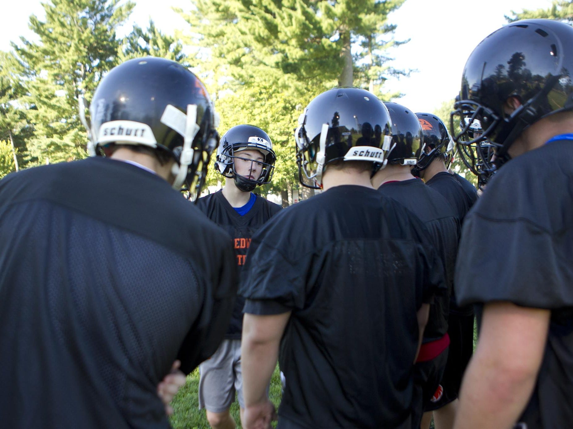 Quarterback Ian Gibbs huddles up with his teammates during the first day of football practice at John Edwards High School, Tuesday, Aug. 4, 2015.