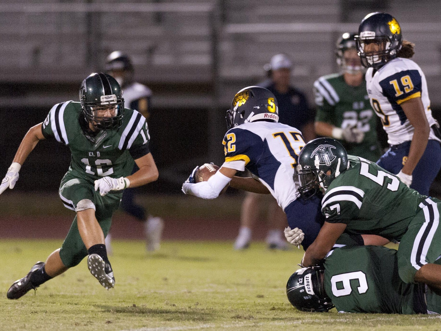 El Diamante's Zach McCorvey rushes to assist Alec Pierce and Gerry Hernandez in taking down Sunnyside's Raymond Hernandez in a Sept. 4 game.