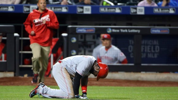Cincinnati Reds second baseman Brandon Phillips (4) falls to the ground after being hit by a pitch during the fourth inning against the New York Mets at Citi Field.