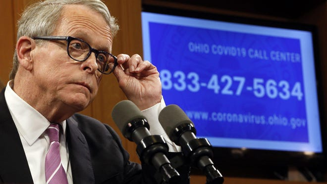 In this March 10, 2020 file photo, Gov. Mike DeWine adjusts his glasses while suggesting guidelines for Ohioans to deal with the coronavirus including not attending indoor events including sports at a press conference at the Ohio Statehouse.