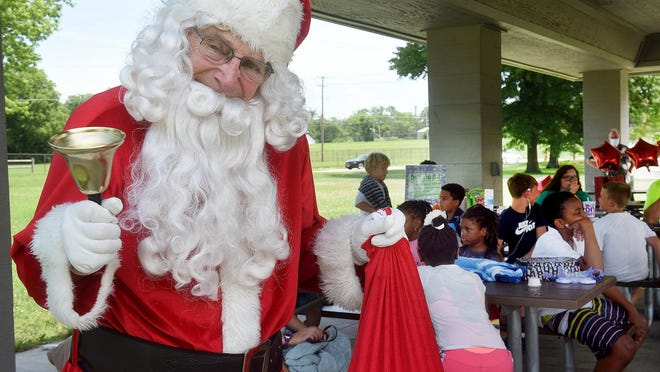 Don Waltman dug out his lightest Santa Claus suit Thursday to entertain children at Douglass Park participating in the Lunch in the Park program and the Voluntary Action Center's annual Christmas in July fundraiser. Other stops were Mary Lee Johnston Community Learning Center, Park Avenue Head Start and Nora Stewart Memorial Nursery School. Children were given a gift bag with play-doh, candy canes, a book, notebook and markers. Lunch in the Park is a free meal program offered by the Columbia/Boone County Health Department and the city of Columbia.