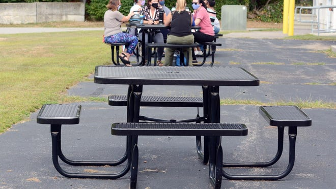Stanton Elementary School staff eat lunch at an outdoor picnic table. Norwich Public Schools Education Foundation donated over $20,000 worth of picnic tables to the district, which volunteers placed at early learning centers and elementary schools.