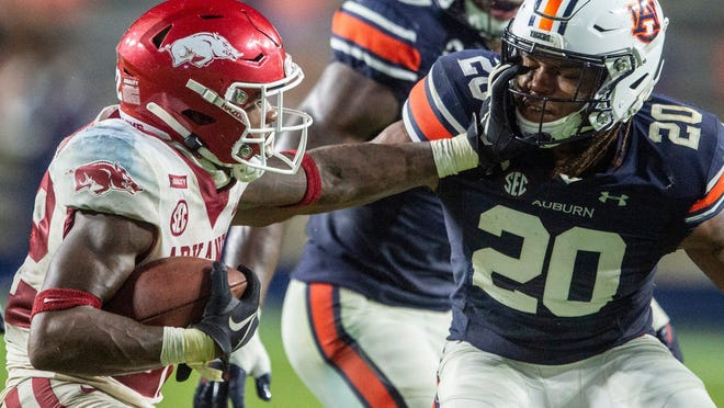 Arkansas running back Trelon Smith (22) stiff arms Auburn defensive back Jamien Sherwood (20) at Jordan Hare Stadium in Auburn, Ala., on Saturday, Oct. 10, 2020. Auburn defeated Arkansas 30-28.