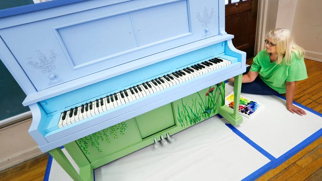 """Jeannette Rehmel paints an upright piano for """"Pianos in the Street"""" Tuesday at Morton Community Center. Tippecanoe Music Teachers Association is organizing the public arts event, which will place several pianos outdoors for the public to play. Rehmel is calling her painting, which features lots of flowers, """"Concert in Monet's Garden."""""""