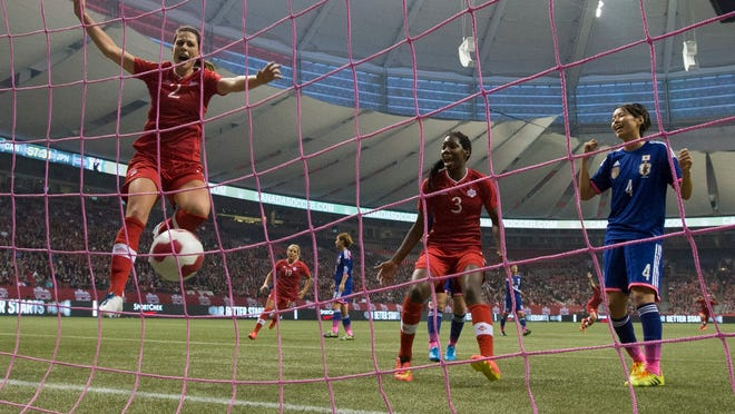 Team Canada's Emily Zurrer, left, and Kadeisha Buchanan, center, celebrate teammate Sophie Schmidt's goal as Japan's Saki Kumagai looks on during second half of International friendly soccer action Tuesday, Oct. 28, 2014 in Vancouver, British Columbia.  (AP Photo/The Canadian Press, Jonathan Hayward)