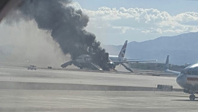 Smoke billows out from a plane that caught fire at McCarren International Airport in Las Vegas. An engine on the British Airways plane caught fire before takeoff, forcing passengers to escape on emergency slides.