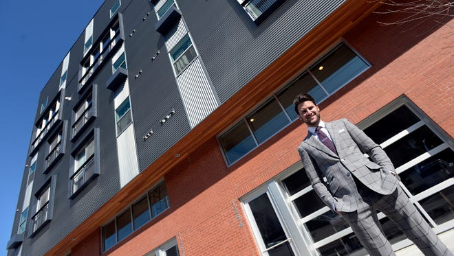 Stephen Richards poses for a photo in front of his live-work townhome in Wedgewood-Houston. His shop, Richards Bespoke, a men's custom clothier, is at street level.