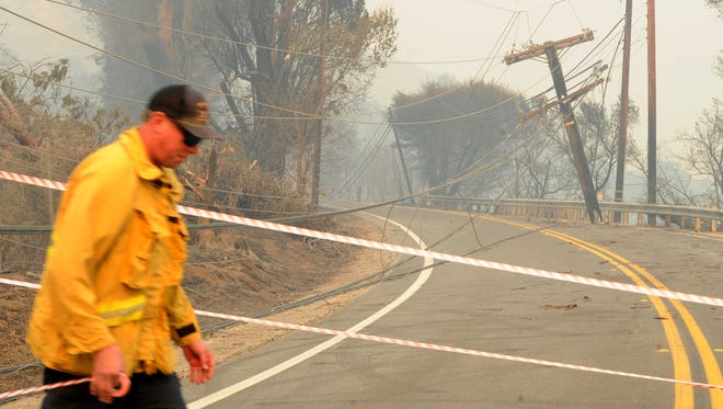 The Thomas Fire brought power lines down on Highway 150 near Santa Paula in December as firefighter Robert Bucho, of Orange County, taped it off in this file photo.