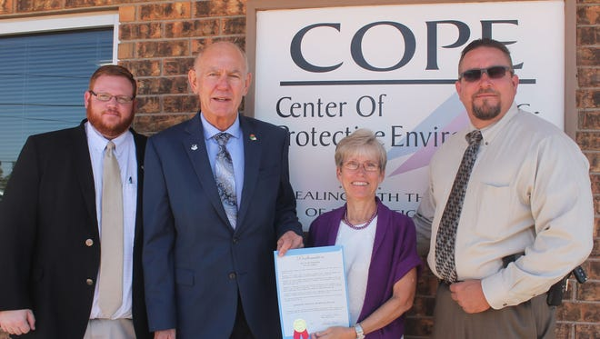 Twelfth Judicial District Attorney John Sugg, Mayor Richard Boss, COPE Executive Director Kay Gomolak and Alamogordo Police Chief Daron Syling celebrate the Center of Protective Environment's newly renovated facility.