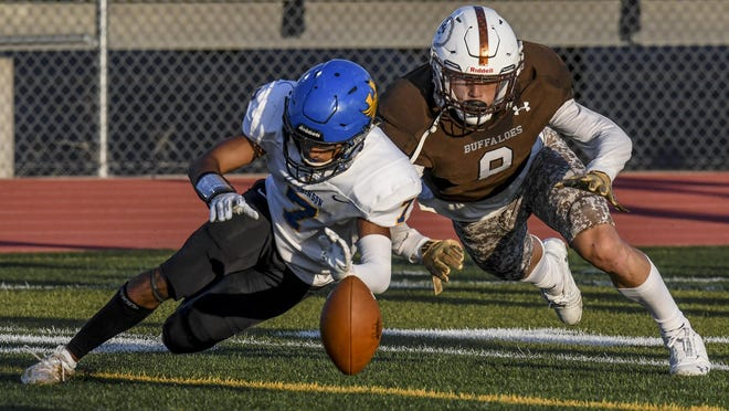 Garden City High School defensive back Cooper Ramsey, right, battles Hutchinson's Noah Khokhar for control of a fumble off an errant Salthawks' pitch Friday at Buffalo Stadium. Khokhar was able to recover the ball, which resulted in a 10-yard loss for Hutchinson.