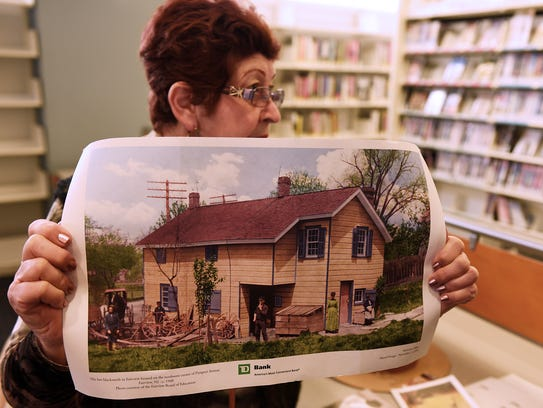 Mazzeo holds a photograph of the home that Douglas