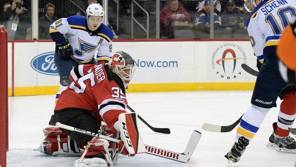New Jersey Devils goalie Cory Schneider (35) deflects