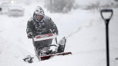 Robert Santiago helps snow blow the driveways of his neighbors on Ave D in the city during a February 2015 snowstorm.
