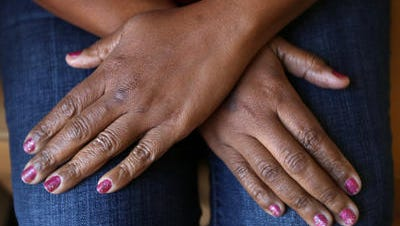Hands of a domestic abuse victim are seen at the Julian Center, a center that supports victims of domestic violence and sexual assault.