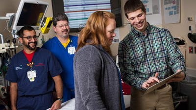 University of Wisconsin-Milwaukee student app developer Evan Timmermann shows the First Five Minutes app to physicians Amy Drendel, Danny Thomas (left) and Michael Meyer. They are part of a team that developed the app, which allows ER physicians to quickly calculate dosages for children they are resuscitating.