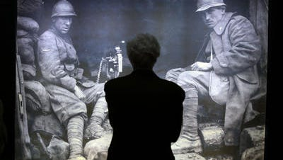 A man stands in front a WWI picture in the museum at Italy's Tomb of the Unknown Soldier in Rome, Friday, May 30, 2014. The museum will display previously unpublished World War I images and documents to commemorate the 100th anniversary of the country's involvement in the bloodshed. The exhibit contains censored images of executions and prisoners of war, as well as notifications for military tribunal death sentences that were posted on the streets of Rome. It also includes videos from the war, letters and diaries from soldiers, and recent photography that revisits the remains of trenches, shelters and villages.