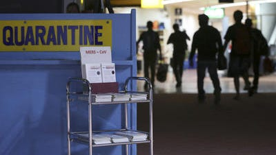 Passengers walk past the medical quarantine area showing information sheets for the Middle East respiratory syndrome coronavirus at the arrival section of Manila's International Airport in April.
