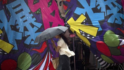 A Chinese woman holds an umbrella while walking past a clothing booth during a promotional sale outside a shopping mall on a rainy day in Beijing, China Tuesday, June 10, 2014. Global stock markets mostly fell on Monday amid concerns about turmoil in Iraq and as a weak European economic report offset a more upbeat one in China.