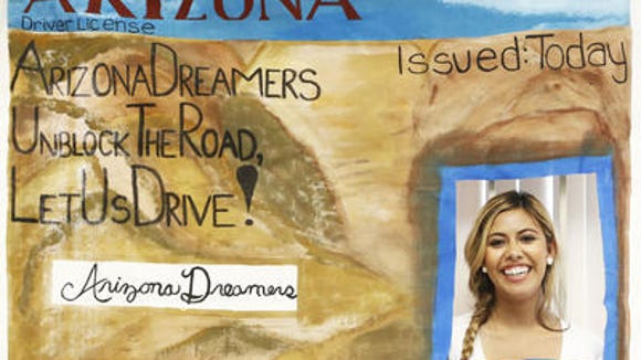 A young DREAMer poses in a replica of a driver's license