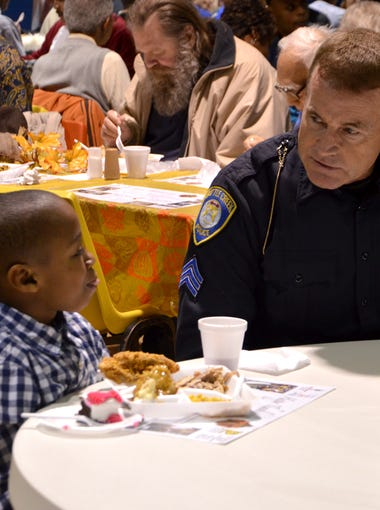 Battle Creek Police Officer Brad Palmer sits with 9-year-old Brandon Mcgee during the Thanksgiving dinner at Washington Heights United Methodist Church.