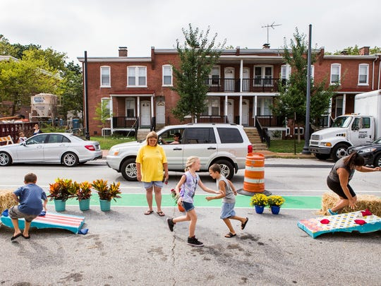 Kids play corn hole along Union Street in Wilmington as part of the Better Block Project on Monday evening.