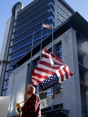 In this Sept. 13, 2016, file photo, a protester flies an upside down United States flag outside the federal courthouse in Portland, Oregon, during the trial for Ammon and Ryan Bundy and five others over the occupation of the Malheur National Wildlife Refuge.