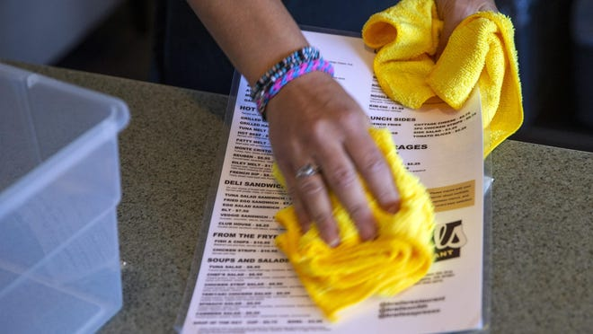 Menus are wiped down after each customer at Brail's Restaurant. [Andy Nelson/The Register-Guard] - registerguard.com