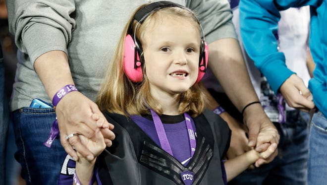 Abby Faber of Iowa stands in the end zone with here family during a presentation where they were introduced during the first half of an NCAA college football game between West Virginia and TCU Thursday, Oct. 29, 2015, in Fort Worth, Texas.
