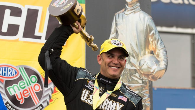 Top Fuel winner Tony Schumacher hoists his trophy at the Carquest Auto Parts NHRA Nationals at Wild Horse Pass Motorsports Park near Chandler on Sunday, Feb. 22, 2015.