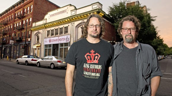 Partners Chris Schadler and Dan McCabe stand with the Woodward Theater in the background.