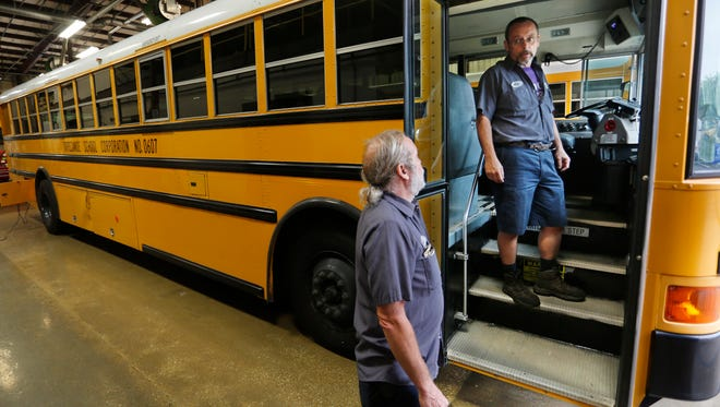 Alan Fidler, right, trouble shoots the video monitoring system on a bus with Jim Martin Wednesday, July 23, 2014, in the Tippecanoe School Corp. bus garage in Lafayette. Fidler and fellow bus mechanic Chuck Schneidt were recognized as national champion bus mechanics.