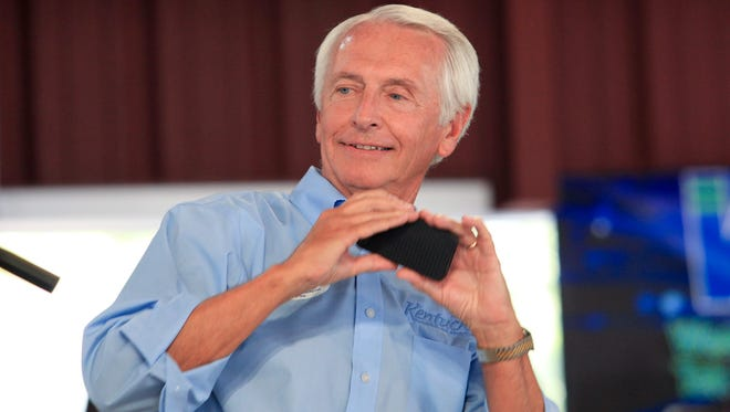 Gov. Steve Beshear took out his cell phone to take a photo of himself with U.S. Sen. Mitch McConnell as a reminder before he said that Alison Lundergan Grimes would retire the senator at the Fancy Farm Picnic.  Aug. 2, 2014