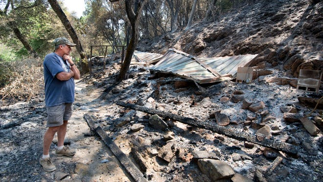 Bill Cleek looks over the remains of one of his cabins which was destroyed by a fire at his Rancho Cicada Retreat in Amador County, Sunday, July 27, 2014, in Plymouth, Calif. Firefighters in Northern California on Sunday battled a wildfire that has destroyed 10 homes and forced hundreds of evacuations in the Sierra Nevada foothills, while a fire near Yosemite National Park destroyed one home and grew significantly overnight. (AP Photo/The Sacramento Bee, Randy Pench)