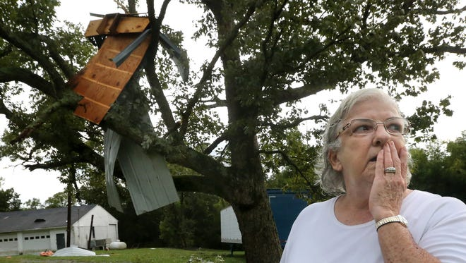 Sandra Scott looks over her property after a storm ripped the roof off of her home leaving part of the debris in the tree behind her, on Wednesday August  20, 2014.