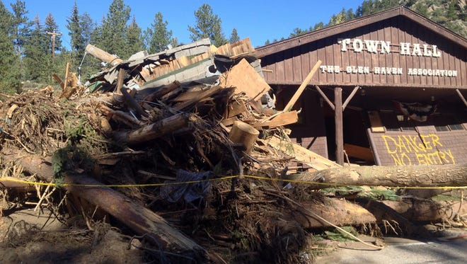 A massive pile of debris sits on the upstream side of the Glen Haven (Colo.) Town Hall on Sept. 24, 2013. The recent raging flood waters shoved an SUV into the building, which then partially collapsed atop it.